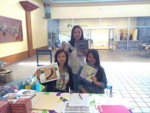 Thao (right) helping out at a citizenship fair that merged nail salon health information in 2014